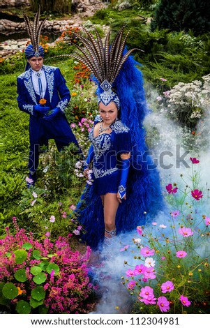 Couple in expensive dark blue costume of illusionist pose in fairy tale flowers park.