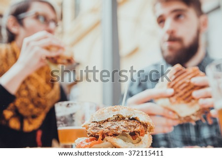 Couple In Fast Food Restaurant Eating Burgers. Focus Is On Burger - stock photo