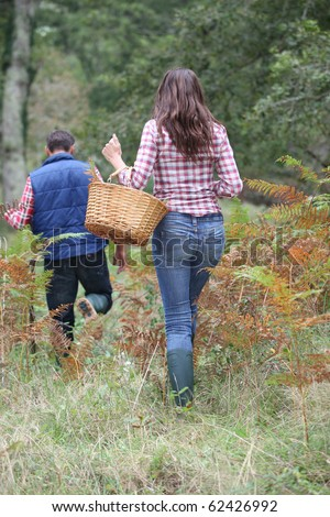 Couple in forest picking mushrooms in autumn