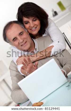 Couple in front of a laptop - stock photo
