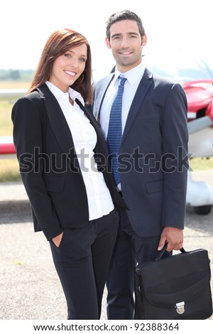 Couple in front of airplane - stock photo