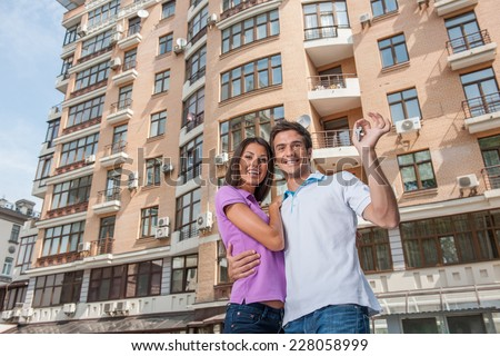 Couple in front of new home holding door keys. man hugging womam and holding apartment keys - stock photo