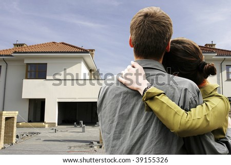 couple in  front of one-family house in modern residential area - stock photo