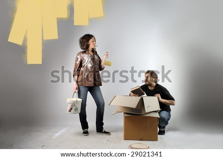 Couple in front of partially painted wall in home - stock photo