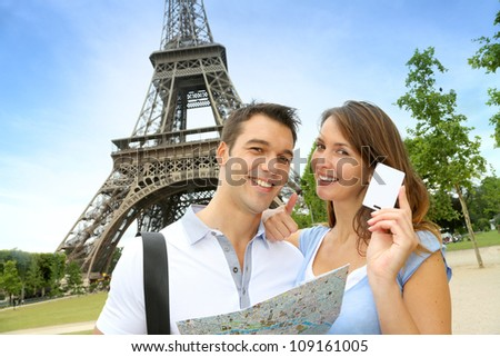 Couple in front of the Eiffel tower holding tourist pass - stock photo