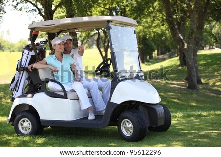 Couple in golf buggy - stock photo