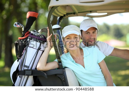 Couple in golf cart - stock photo