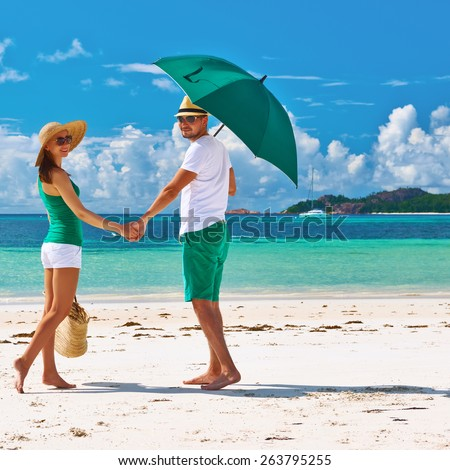 Couple in green with umbrella on a tropical beach at Seychelles - stock photo
