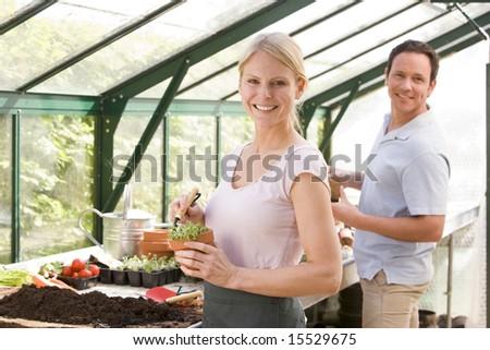 Couple in greenhouse raking soil in pots smiling - stock photo