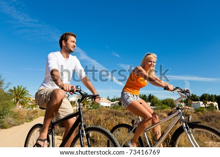 Couple in holidays cycling under a blue sky in the dunes on a beach - stock photo