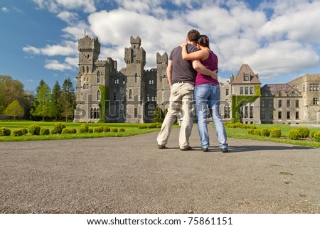 Couple in hug looking to the idyllic Ashford castle - Ireland