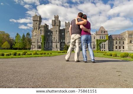Couple in hug looking to the idyllic Ashford castle - Ireland - stock photo