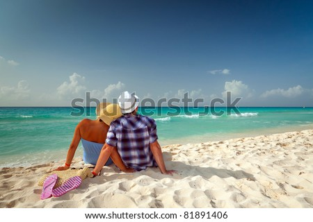 Couple in hug looking together on the Caribbean Sea - stock photo