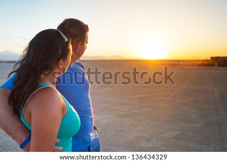 Couple in hug watching together sunset on the desert