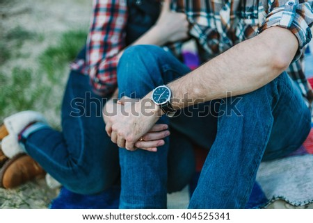 Couple in jeans and plaid shirts sitting and holding hands. Shallow focus. - stock photo