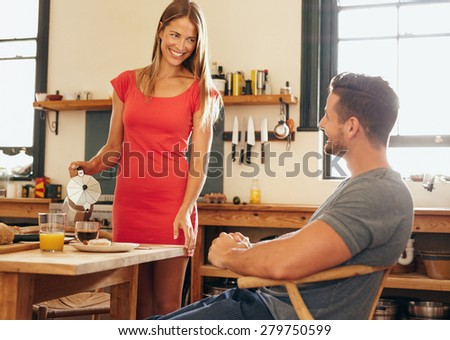 Couple in kitchen at breakfast table. Young woman serving coffee to her boyfriend sitting on chair. Young couple looking at each other and smiling. - stock photo