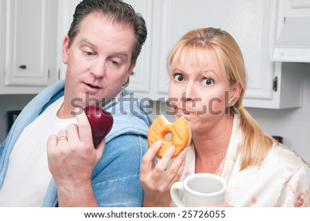 Couple in Kitchen Eating Donut and Coffee or Healthy Fruit.