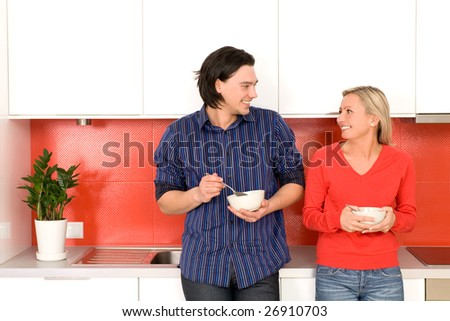 Couple in kitchen holding bowls - stock photo