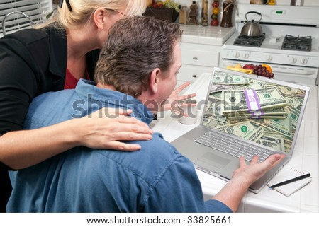 Couple In Kitchen Using Laptop to Earn or Win Money. Screen image can easily be replaced using the included clipping path. - stock photo
