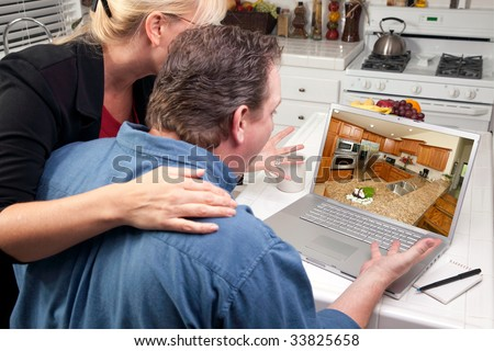 Couple In Kitchen Using Laptop to Research Home Improvement Ideas. Screen image can easily be replaced using the included clipping path. - stock photo