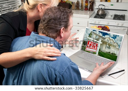 Couple In Kitchen Using Laptop to Research Real Estate. Screen image can easily be replaced using the included clipping path. - stock photo