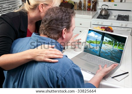 Couple In Kitchen Using Laptop to Research Travel and Vacations. Screen image can easily be replaced using the included clipping path. - stock photo