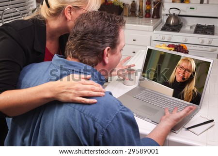 Couple In Kitchen Using Laptop with Customer Support Woman on the Screen. - stock photo