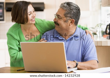 Couple in kitchen with laptop smiling - stock photo