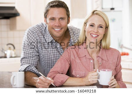 Couple in kitchen with newspaper and coffee smiling - stock photo