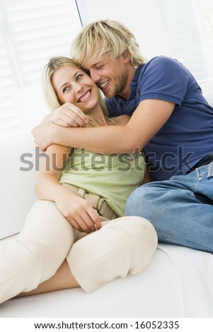 Couple in living room hugging and smiling - stock photo