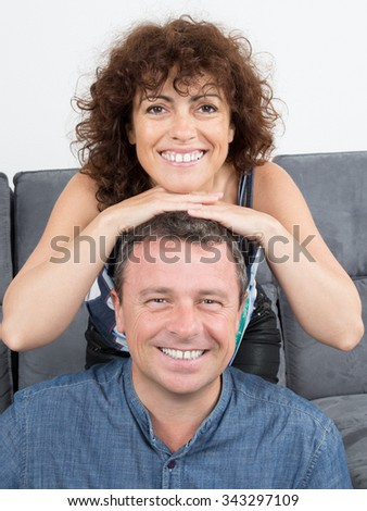 Couple in living room smiling and laughing at home - stock photo
