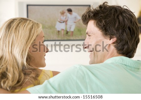 Couple in living room watching television smiling - stock photo