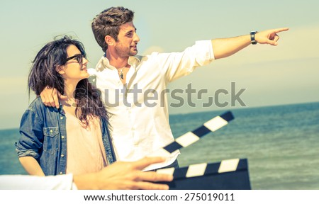 Couple in love acting for romantic movie at beach - Cinema industry concept with ciak slate - Confident guy and happy girlfriend modern lifestyle - Focus on male face and soft vintage filtered look - stock photo