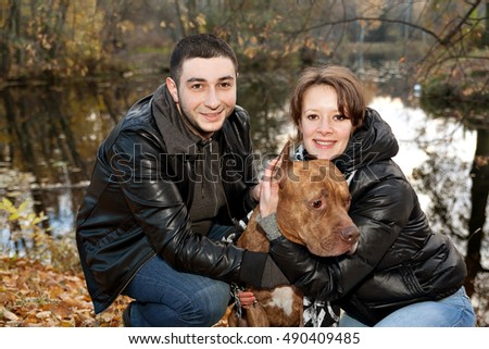 Couple in love and American Pit Bull Terrier in the autumn park