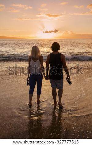 Couple in love and holding hands at the beach at sunset - stock photo