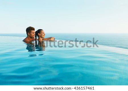 Couple In Love At Luxury Resort On Romantic Summer Vacation. People Relaxing Together In Edge Swimming Pool Water, Enjoying Beautiful Sea View. Happy Lovers On Honeymoon Travel. Relationship, Romance - stock photo