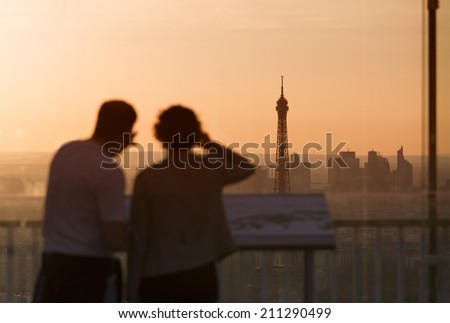 Couple in love at Paris admire Eiffel Tower at sunset - stock photo