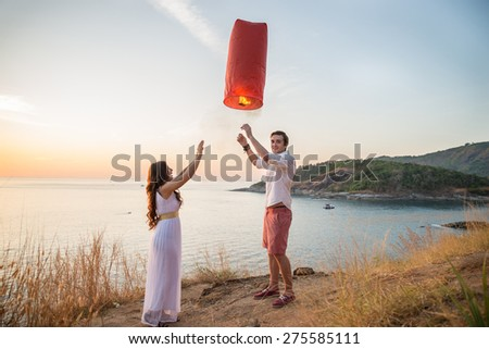 Couple in love at sunset releasing a lantern for good luck - Lovers on a romantic date outdoors and natural landscape in the background - stock photo