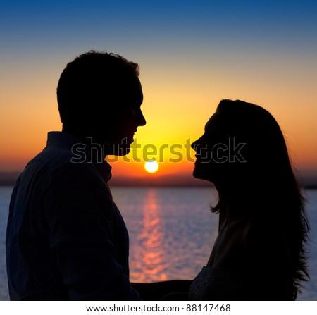 couple in love back light silhouette at lake orange sunset - stock photo
