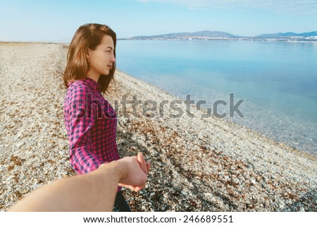 Couple in love. Beautiful young woman holding man's hand and leading him on beach near the sea. Point of view shot - stock photo