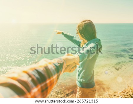 Couple in love. Beautiful young woman holding man's hand and showing him something in distance the sea. Image with sunlight effect. Point of view shot - stock photo