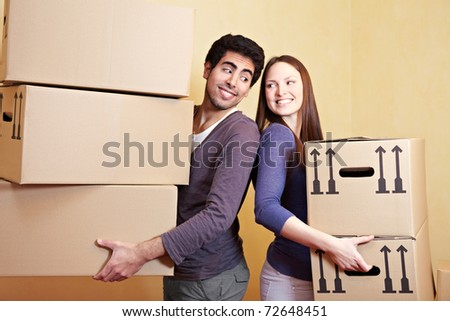 Couple in love carrying many moving boxes into their new home - stock photo