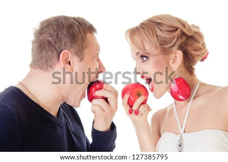 Couple in love - Caucasian man and woman eat apples. emotional portrait in the studio, isolated on white background - stock photo