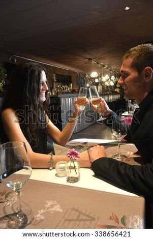 couple in love dining at an elegant restaurant and toasting with champagne - stock photo