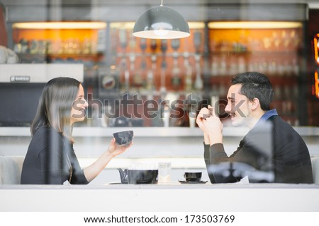 Couple in love drinking coffee laughing in cafe - stock photo