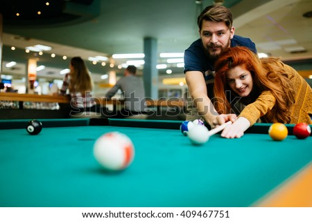 Couple in love enjoying playing billiard in snooker bar - stock photo