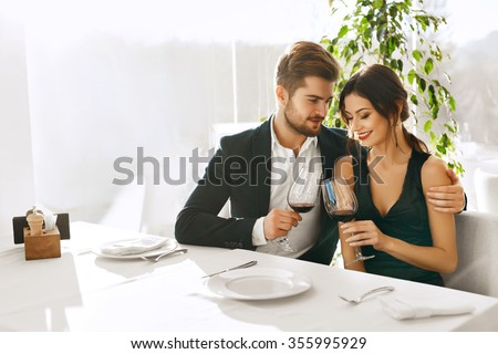 Couple In Love. Happy Romantic Smiling Elegant People Having Dinner, Drinking Wine, Celebrating Holiday, Anniversary Or Valentine's Day In Gourmet Restaurant. Romance, Relationships Concept. - stock photo