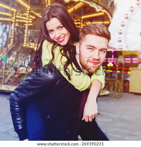 Couple in love have fun and laughing and  enjoying together being in an amusement park. Pretty girl sitting on the back of her boyfriend. - stock photo