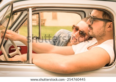 Couple in love having a rest during honeymoon vintage car trip - Hipster lifestyle traveling around the world with classic car - Young people enjoying happy moments of life - Warm retro filtered look - stock photo