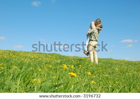 Couple in love having fun on spring meadow - stock photo
